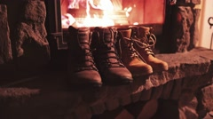 Woman Hand takes Winter Boots from a Shelf near Cozy Burning Fireplace. 4K. Stock Footage