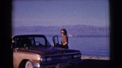 1961: woman blowing kisses beside car at beach CLARKSDALE, ARIZONA Stock Footage