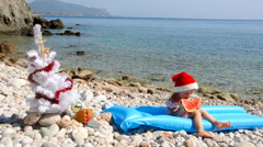 Young girl in chrismas hat is eating watermelon on the beach Stock Footage