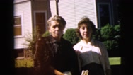1962: two women posing in front of a light-gray house while one is smoking  Stock Footage