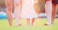 Little baby First Steps. Family feet walk on grass Close Up . SLOW MOTION 4K Stock Footage