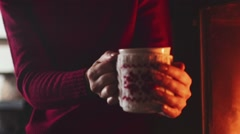 Woman Hands Holding Coffee or Tea Cup by Cozy burning Fireplace. 4K STABILIZED Stock Footage