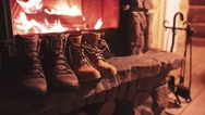 Woman Hand puts Winter Boots on a Shelf near Cozy Burning Fireplace. 4K. Stock Footage