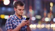 Man using smart phone at night in city. 4K. Busy Street lights background. Stock Footage