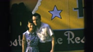 1962: happy couple pose for a snap in front of large banner CAMDEN, NEW JERSEY Stock Footage