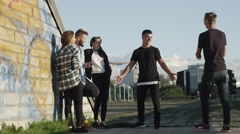 Young Man Coming and Greeting Group of Teenager Friends Hanging Out Outdoors  Stock Footage