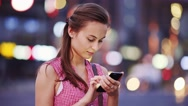 Woman using smart phone at night in city. 4K. Busy Street lights background. Stock Footage