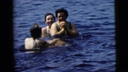 1962: a family takes a refreshingly cold dip in a pond on a sunny day. CAMDEN Stock Footage