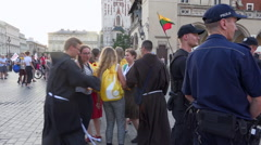Police officers group on crowded square with teenagers dancing, Krakow - Zoom in Stock Footage