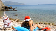 Young woman relaxing on the beach with christmas tree Stock Footage