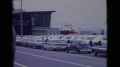 1968: old woman walking on the pedestrian path near to the car parked area  Stock Footage