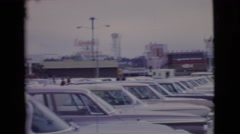1968: women are walking by a parking lot area full of cars  Stock Footage