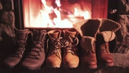 Winter Boots drying in front of a Cozy Burning Fireplace 4K. Stock Footage