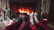Feet in woollen socks by the Cozy Burning Christmas fireplace. 4K. Stock Footage