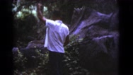 1964: a man in the woods raising his hand into the air and gesturing COTTONWOOD Stock Footage