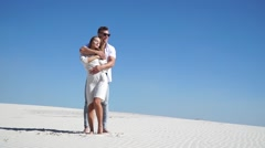 Loving couple embracing in the desert in the wind Stock Footage
