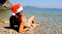 Young woman relaxing on the beach with christmas hat Stock Footage