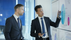 4K Businessmen having a discussion, looking at video screen with charts & graphs Stock Footage