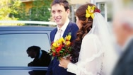 Happy married couple stand by the car in wedding day and laughing in slowmotion Stock Footage