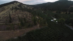 Aerial: Small house in a Orchard and Mountain Vista, Horror-Equse Stock Footage