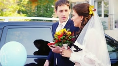Happy married couple stand by the car in wedding day in slowmotion. 1920x1080 Stock Footage
