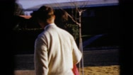 1968: an attractive couple walking to the car and the young man opens the car Stock Footage