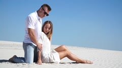 Loving couple sitting on the sand in the desert Stock Footage