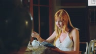 Young woman eating ice cream in rustic cafe, reading magazine Stock Footage