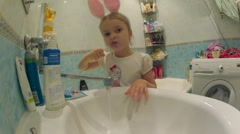 Little girl brushing her teeth and rinse mouth above bathroom sink. Time Lapse Stock Footage
