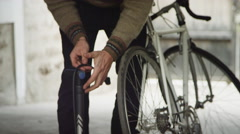 Bicycle Mechanic pumping up tires in shop Stock Footage