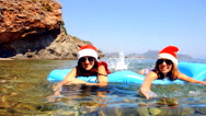 Beautiful young women are swimming in the sea with christmas hat Stock Footage