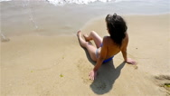 Woman relaxing on the beach, waves splashing in her body, slow motion Stock Footage