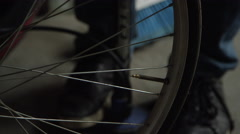 Bicycle mechanic pumping up tire Stock Footage