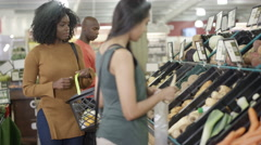 4K Customers shopping for groceries in the supermarket with focus on young woman Arkistovideo