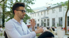 Elegant man talking on loudspeaker in the outdoor cafe and drinking coffee Stock Footage