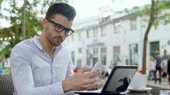 Man using modern technology and receives good news in the outdoor cafe Stock Footage