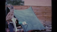 1968: two boys wash and dry dishes in front of a tent set up in the yard. Stock Footage