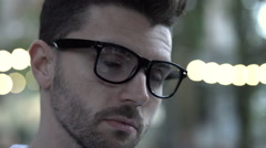 Calm man wearing glasses and looking thoughtful, steadycam shot Stock Footage