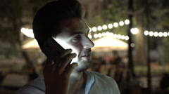 Man standing at night in public place and talking on cellphone Stock Footage