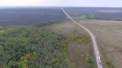 Aerial - Cars Driving On The Road That Cuts Through The Green Landscape Stock Footage