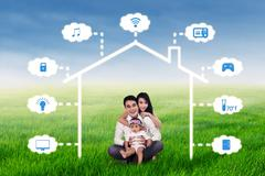 Family sits at field under smart house design Stock Photos