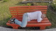 Man in jeans and a shirt sleeping on a bench under the open sky Stock Footage