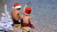 Kids in chrismas hat are playing with chrismas attribbute on the beach Stock Footage