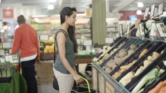 4K Customers shopping for groceries in the supermarket with focus on young woman Stock Footage