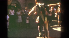 1962: a man on the street in a costume performing on a unicycle  Stock Footage