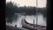 1962: group of people slowly rowing down a river in the woods with calm water. Stock Footage