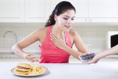 Young woman avoid burger and choose blueberry Stock Photos
