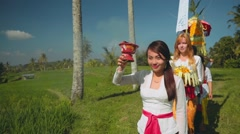 Balinese procession going through rice fields with offerings Stock Footage