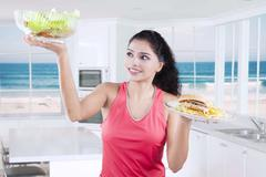 Young woman with unhealthy and healthy food Stock Photos