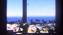 1962: picturesque seaside view from a hotel window of blue ocean and trees  Stock Footage